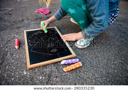 Girl drawing a house on chalkboard outdoors on asphalt with colorful street chalk - stock photo