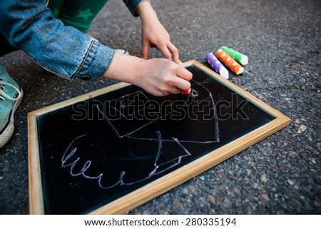 Girl drawing a house on chalkboard outdoors with colorful street chalk - stock photo