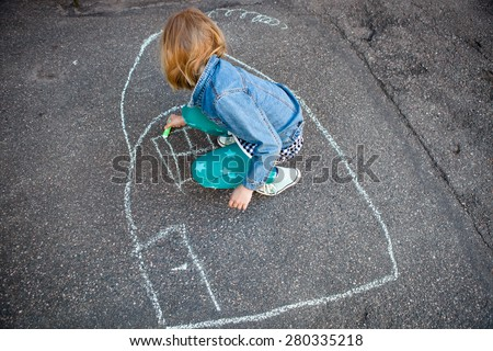 Girl drawing a picture of a house on asphalt with street chalk - stock photo
