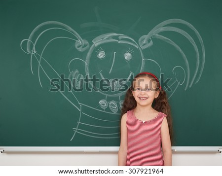 girl drawing faces on the school board - stock photo