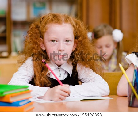 girl drawing in copybook in classroom. looking at camera