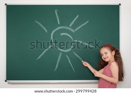 girl drawing sun by white chalk on school board - stock photo