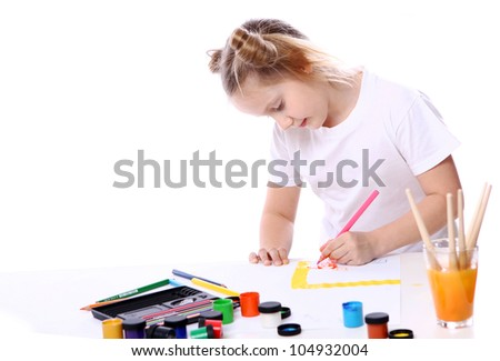 Girl drawing with brush and paint over white background