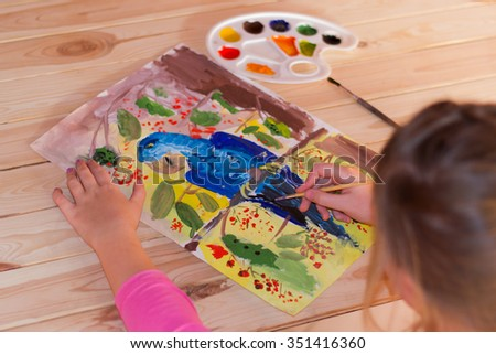 Girl draws a large parrot gouache on paper in warm colors - stock photo