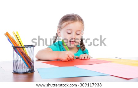 girl draws at the table on a white background - stock photo