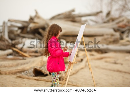 girl draws on the easel outdoors - stock photo