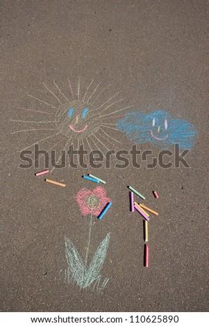 Girl draws on the pavement - stock photo