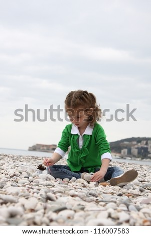 Girl draws on the sea on the stones and pebbles