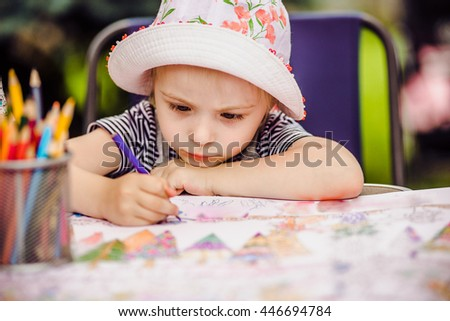 girl draws with crayons. colored pencils in a glass on the table - stock photo