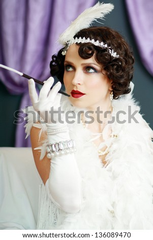 Girl dreaming beautiful young flapper woman lady from roaring 20s looking at camera. Blue tint on image. - stock photo