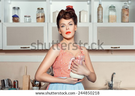 Girl dreams of standing in the kitchen, in the hands of her milk jug.