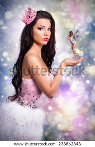 girl dressed as a princess fairy holds in his hands. fantastic brunette doll on a colorful background, close elf flies