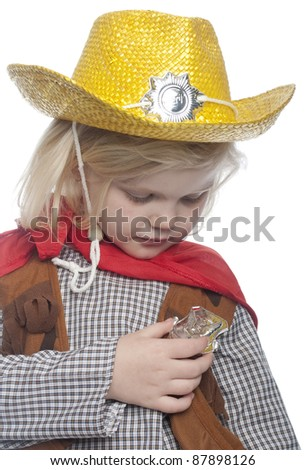 Girl dressed as cowgirl, looking directly at her badge, located on her shirt