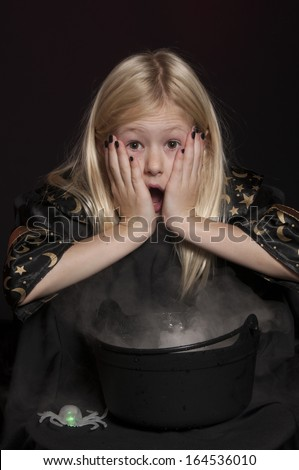 girl dressed as Halloween witch isolated on dark background