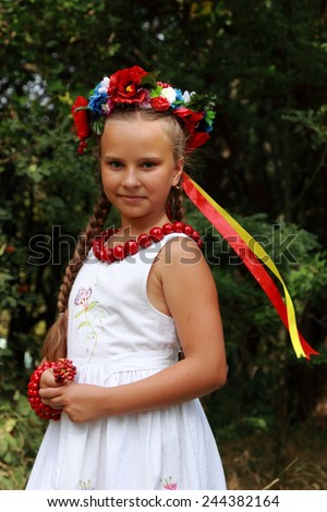 girl dressed in national Ukrainian costume wearing wreath of flowers, peacefully playing in beautiful field in Ukraine - make love not war concept - stock photo