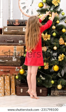 girl dressed in red gown decorating christmas tree indoors - stock photo