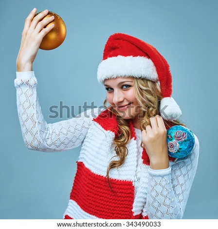 Girl dressed in santa hat  holding a Christmas decoration  balls. She looking at camera. Holiday concept with blue background.