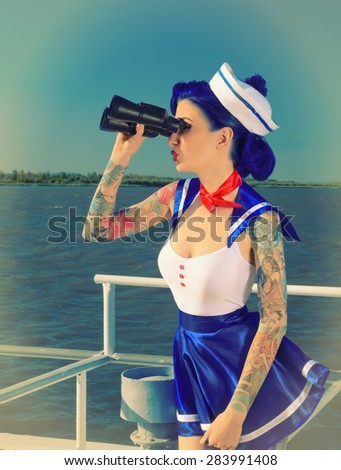 girl dressed sailors looking through binoculars, retro style - stock photo