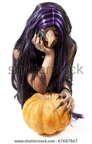 girl dressed up as a witch leaning on a pumpkin - stock photo