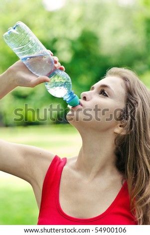 Girl drink water in park after sport - stock photo
