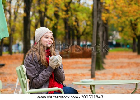 Girl drinking coffee in an outdoor Parisian cafe on a fall day