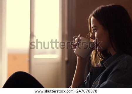 girl drinking coffee in the morning at home - stock photo