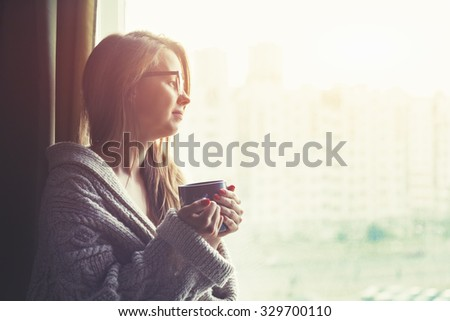 girl drinking coffee or tea in morning sunlight near window - stock photo