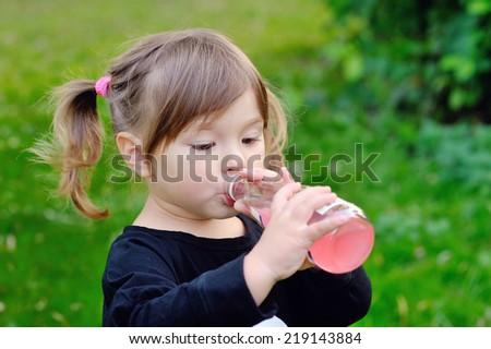 girl drinking from a bottle of lemonade, Outdoors  - stock photo