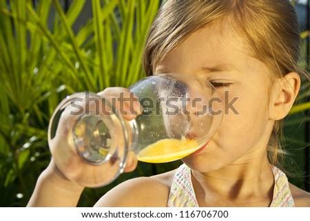 Girl drinking orange juice - stock photo