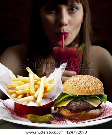 Girl drinking strawberry juice and eating pizza - stock photo