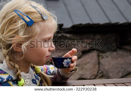 girl drinking tea from ceramics teacup