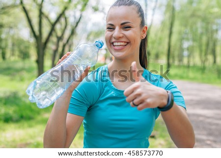 Girl drinking water after treaning in the park