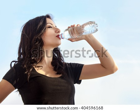 Girl drinking water from a bottle against the sky. She is dressed in sportswear. Concept: fitness, aerobics, health, lifestyle. - stock photo