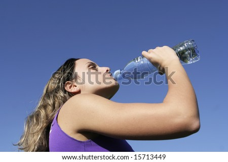 girl drinking water in the park - stock photo