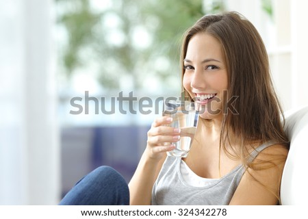 Girl drinking water sitting on a couch at home and looking at camera - stock photo
