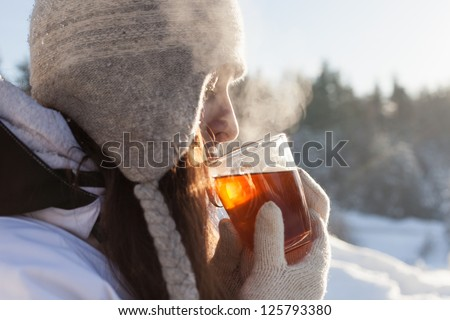 girl drinks tea over winter nature background outdoor - stock photo