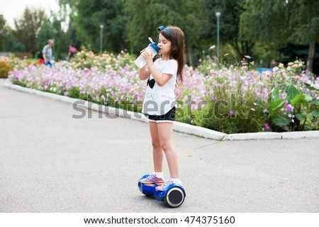 Girl drinks water on hoverboard