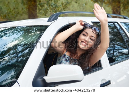 girl driver inside car greeting somebody, look into the distance, has emotions and waves, summer season
