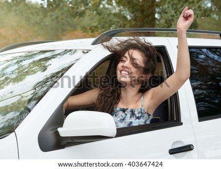 girl driver inside car having fun, look into the distance, has emotions and waves, summer season