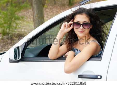 girl driver portrait with sunglasses inside white car - stock photo