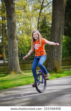 girl driving unicycle outdoors - stock photo