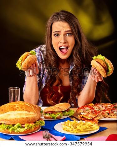 Girl eat fastfood big hamburger and pizza . - stock photo