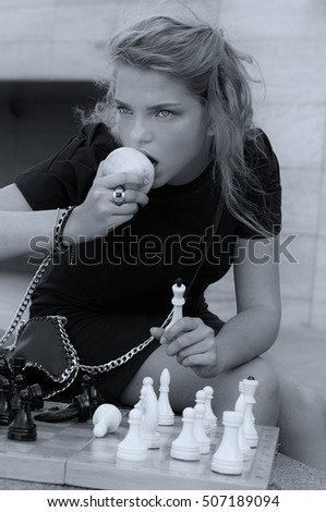 Girl eating an apple while playing chess. Black and white photo in vintage style.