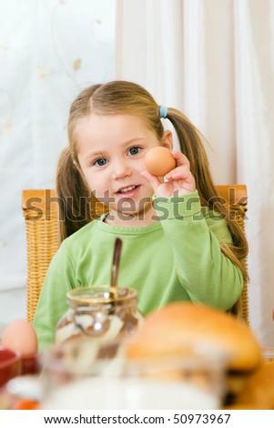 Girl eating an egg for breakfast - stock photo