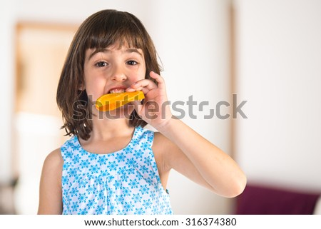 Girl eating an orange slice