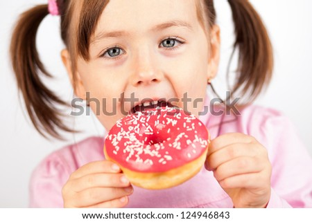 Girl eating an unhealthy doughnut snack.