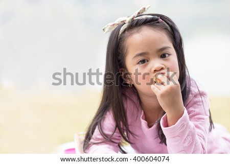 Girl eating cookie or biscuit