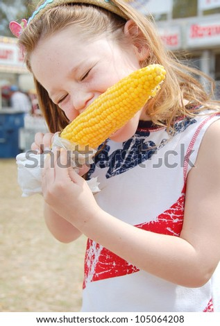 Girl eating corn at fair - stock photo
