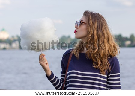 Girl eating cotton candy in the park
