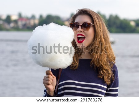Girl eating cotton candy in the park - stock photo